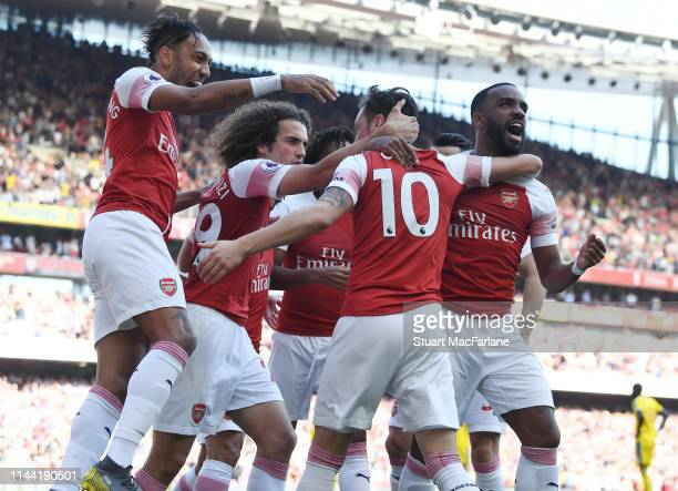 Mesut Ozil celebrates scoring the Arsenal goal with PierreEmerick Aubameyang Matteo Guendouzi and Alex Lacazette during the Premier League match...