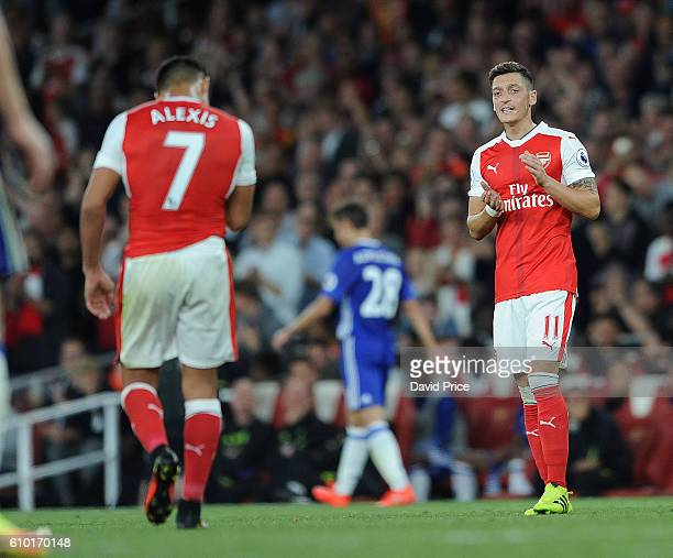 Mesut Ozil claps Alexis Sanchez of Arsenal off the pitch as his is substituted during the Premier League match between Arsenal and Chelsea at...