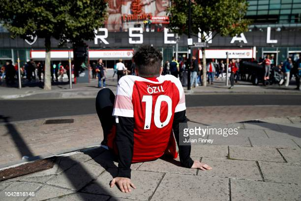 Mesut Ozil fan is seen sat outside the stadium ahead of the Premier League match between Arsenal FC and Watford FC at Emirates Stadium on September...