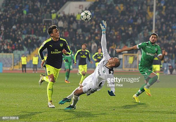 Mesut Ozil knocks the ball past Milan Borjan of Ludogorets on his way to scoring Arsenal's 3rd goal during the UEFA Champions League match between...