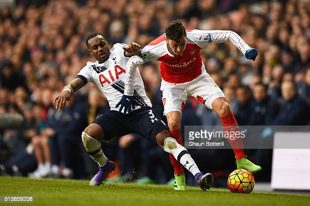 Mesut Ozil of Arsenal and Danny Rose of Tottenham Hotspur compete for the ball during the Barclays Premier League match between Tottenham Hotspur and...