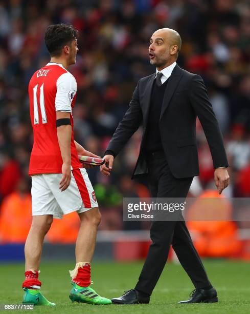 Mesut Ozil of Arsenal and Josep Guardiola Manager of Manchester City argue after the Premier League match between Arsenal and Manchester City at...