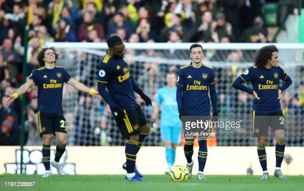 Mesut Ozil of Arsenal and team mates walk back to the half way line during the Premier League match between Norwich City and Arsenal FC at Carrow...