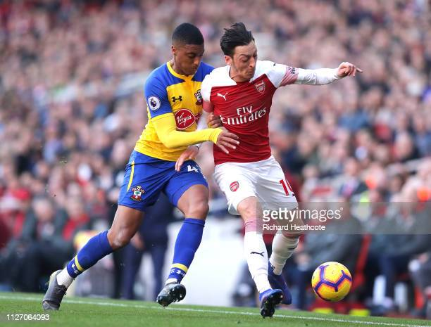 Mesut Ozil of Arsenal battles for possession with Yan Valery of Southampton during the Premier League match between Arsenal FC and Southampton FC at...