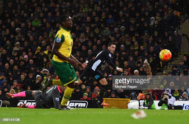 Mesut Ozil of Arsenal beats goalkeeper John Ruddy of Norwich City to score their first goal during the Barclays Premier League match between Norwich...