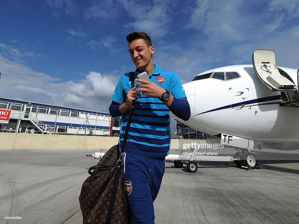 Mesut Ozil of Arsenal boards the team plane at Luton Airport on September 15, 2014 in St Albans, England. Photo by Stuart MacFarlane/Arsenal FC via Getty Images)