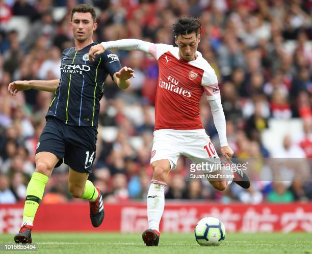 Mesut Ozil of Arsenal breaks past Aymeric Laporte of Man City during the Premier League match between Arsenal FC and Manchester City at Emirates...