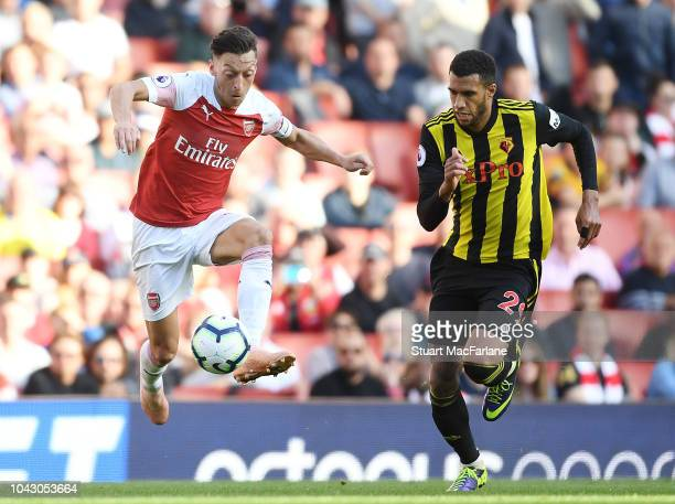 Mesut Ozil of Arsenal breaks past Etienne Capoue of Watford during the Premier League match between Arsenal FC and Watford FC at Emirates Stadium on...