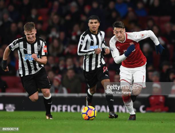 Mesut Ozil of Arsenal breaks past Matt Ritchie of Newcastle during the Premier League match between Arsenal and Newcastle United at Emirates Stadium...