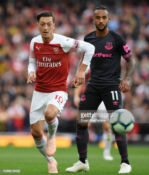 Mesut Ozil of Arsenal breaks past Theo Walcott of Everton during the Premier League match between Arsenal FC and Everton FC at Emirates Stadium on...
