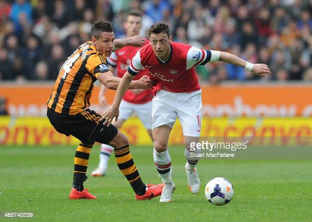 Mesut Ozil of Arsenal breraks past Jake Livermore of Hull during the Barclays Premier League match between Hull City and Arsenal at the KC Stadium on...