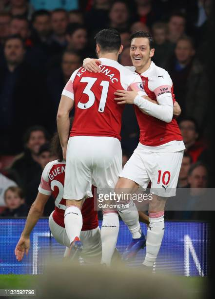 Mesut Ozil of Arsenal celebrates after scoring his team's first goal with Sead Kolasinac of Arsenal during the Premier League match between Arsenal...