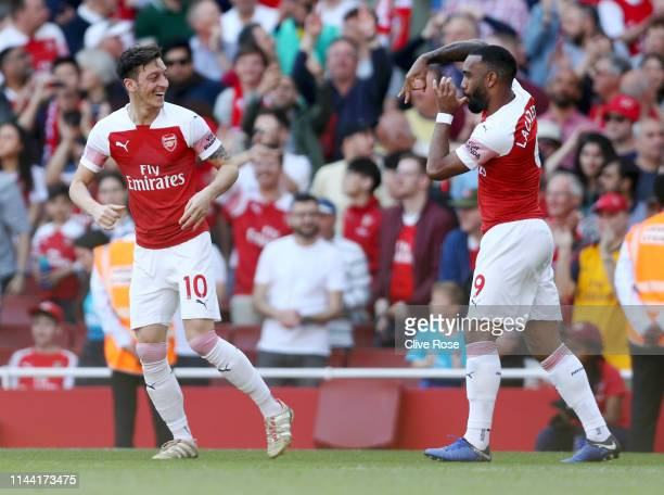 Mesut Ozil of Arsenal celebrates after scoring his team's first goal with Alexandre Lacazette during the Premier League match between Arsenal FC and...