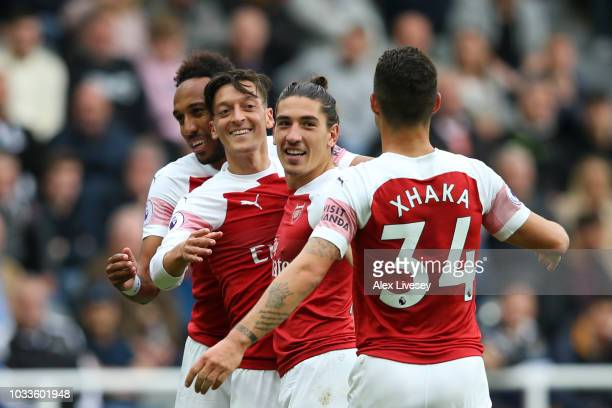 Mesut Ozil of Arsenal celebrates after scoring his team's second goal with team mates during the Premier League match between Newcastle United and...
