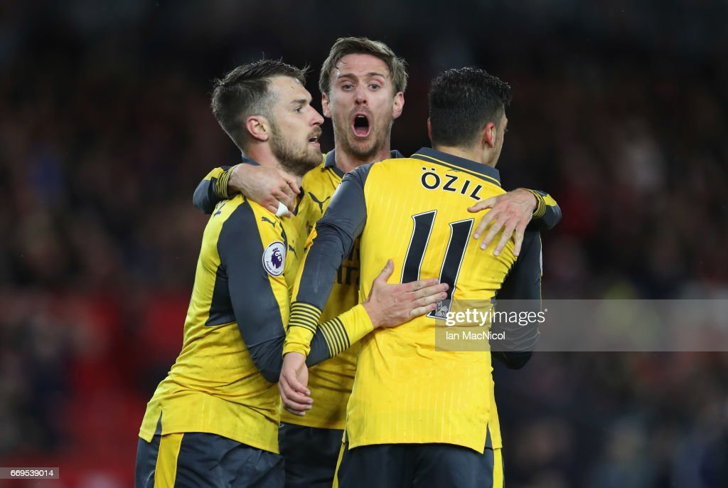 Mesut Ozil of Arsenal (11) celebrates as he scores their second goal with Aaron Ramsey (L) and Nacho Monreal (C) during the Premier League match between Middlesbrough and Arsenal at Riverside Stadium on April 17, 2017 in Middlesbrough, England.