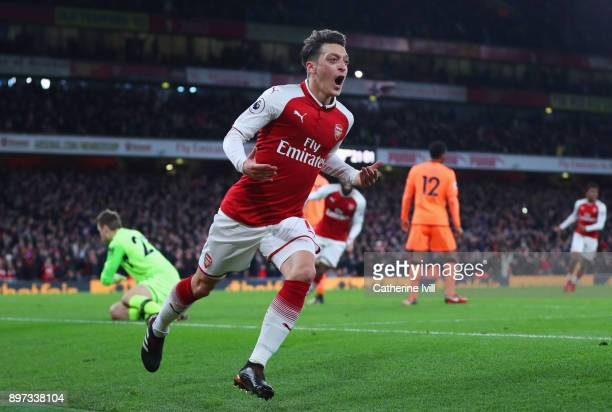 Mesut Ozil of Arsenal celebrates as he scores their third goal wduring the Premier League match between Arsenal and Liverpool at Emirates Stadium on...