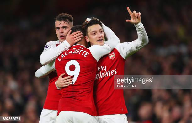Mesut Ozil of Arsenal celebrates as he scores their third goal with Granit Xhaka and Alexandre Lacazette during the Premier League match between...