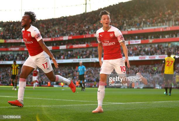 Mesut Ozil of Arsenal celebrates scoring his sides second goal with Alex Iwobi during the Premier League match between Arsenal FC and Watford FC at...