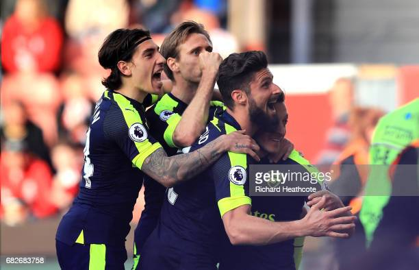 Mesut Ozil of Arsenal celebrates scoring his sides second goal with his Arsenal team mates during the Premier League match between Stoke City and...