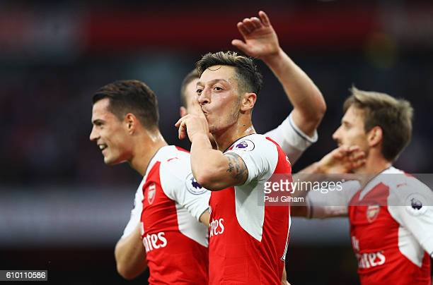 Mesut Ozil of Arsenal celebrates scoring his sides third goal with his team mates during the Premier League match between Arsenal and Chelsea at the...
