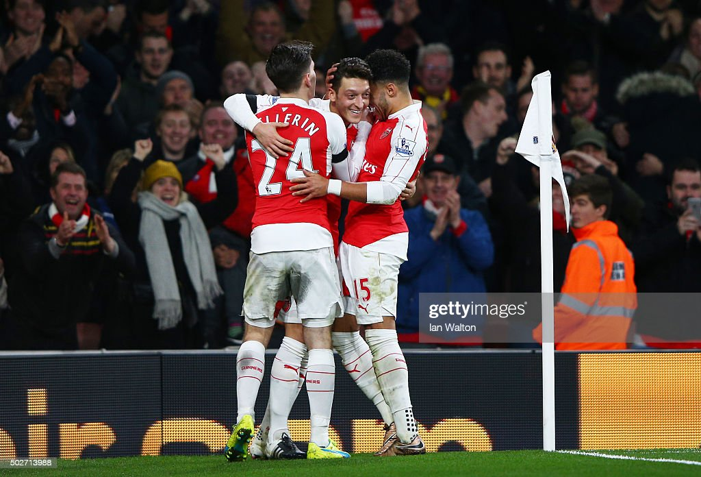 Mesut Ozil (C) of Arsenal celebrates scoring his team's second goal with his team mates Alex Oxlade-Chamberlain (R) and Hector Bellerin (L) during the Barclays Premier League match between Arsenal and A.F.C. Bournemouth at Emirates Stadium on December 28, 2015 in London, England.