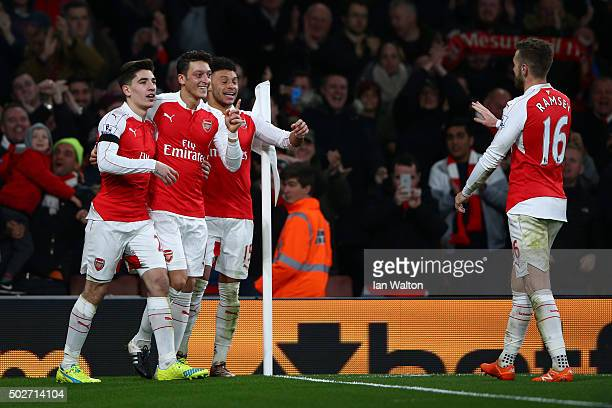 Mesut Ozil of Arsenal celebrates scoring his team's second goal with his team mates Hector Bellerin Alex OxladeChamberlain and Aaron Ramsey during...