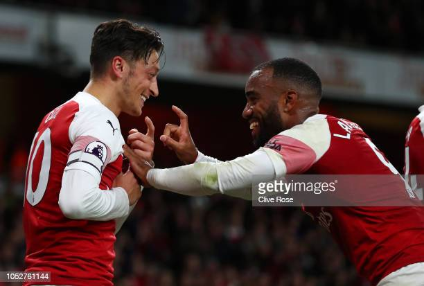 Mesut Ozil of Arsenal celebrates with Alexandre Lacazette of Arsenal after he scores his sides first goal during the Premier League match between...