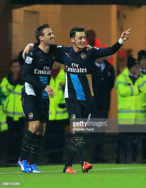 Mesut Ozil of Arsenal celebrates with team mate Nacho Monreal as he scores their first goal during the Barclays Premier League match between Norwich...