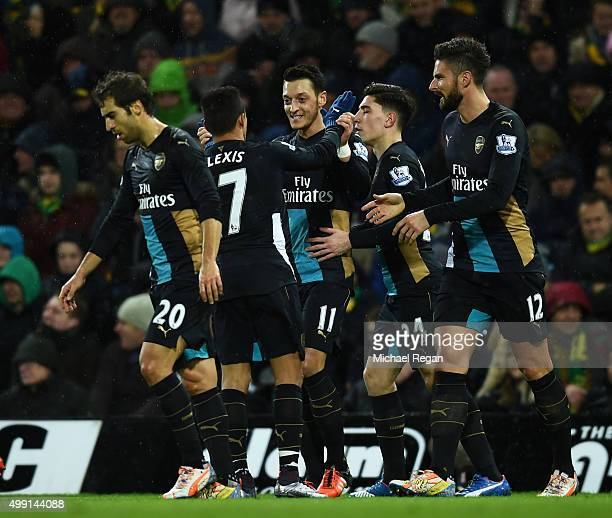 Mesut Ozil of Arsenal celebrates with team mates as he scores their first goal during the Barclays Premier League match between Norwich City and...