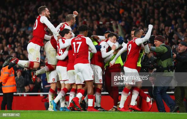 Mesut Ozil of Arsenal celebrates with team mates as he scores their third goal wduring the Premier League match between Arsenal and Liverpool at...