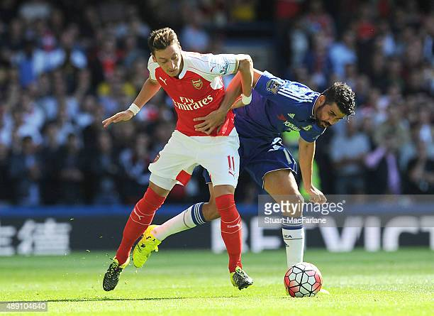 Mesut Ozil of Arsenal challenged by Diego Costa during the Barclays Premier League match between Chelsea and Arsenal on September 19 2015 in London...