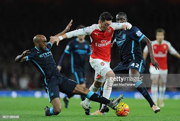 Mesut Ozil of Arsenal challenged by Fabian Delph and Yaya Toure of Man City during the Barclays Premier League match between Arsenal and Manchester...