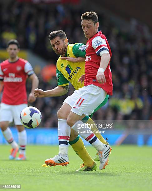 Mesut Ozil of Arsenal challenged by Robert Snodgrass of Norwich during the Barclays Premier League match between Norwich City and Arsenal at Carrow...