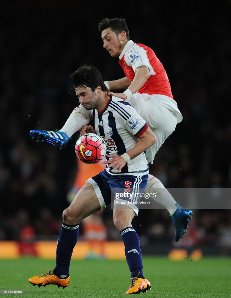 Mesut Ozil of Arsenal challenges Claudio Yacob of WBA during the Barclays Premier League match between Arsenal and West Bromwich Albion at Emirates Stadium on April 21, 2016 in London, England.