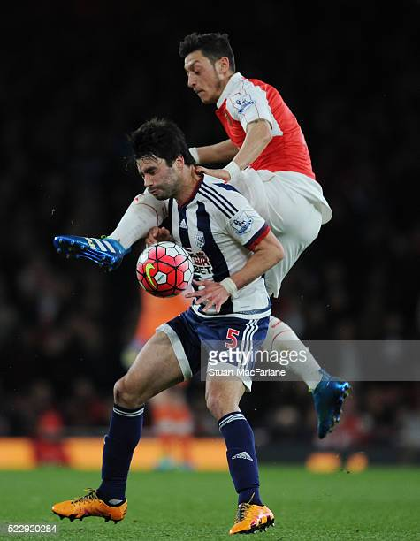 Mesut Ozil of Arsenal challenges Claudio Yacob of WBA during the Barclays Premier League match between Arsenal and West Bromwich Albion at Emirates...