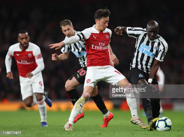 Mesut Ozil of Arsenal competes with Mohamed Diame of Newcastle United during the Premier League match between Arsenal FC and Newcastle United at...