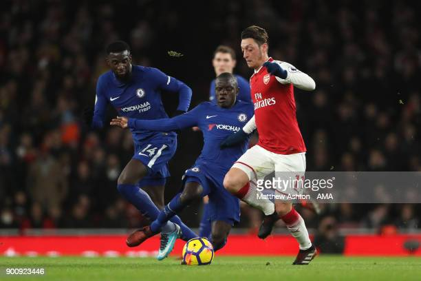 Mesut Ozil of Arsenal competes with N'Golo Kante and Tiemoue Bakayoko of Chelsea during the Premier League match between Arsenal and Chelsea at...