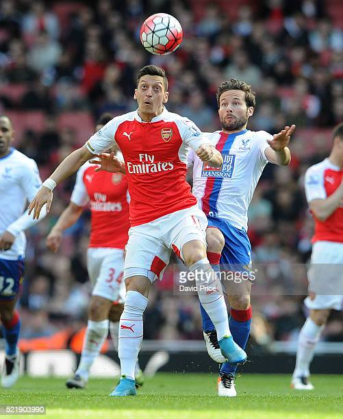 Mesut Ozil of Arsenal controls the ball under pressure from Johan Cabaye of Palace during the Barclays Premier League match between Arsenal and...