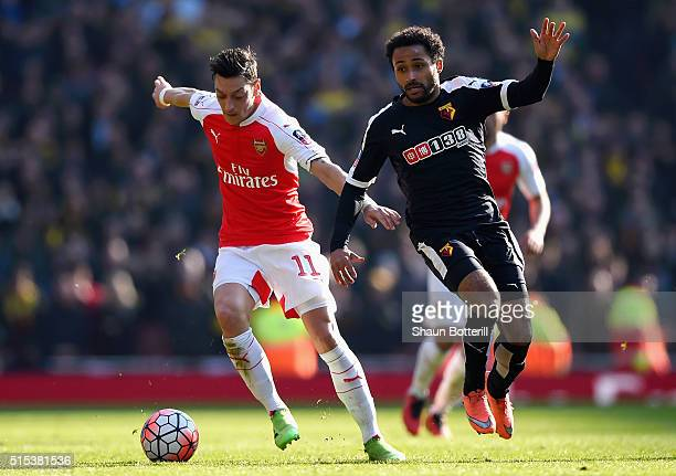 Mesut Ozil of Arsenal evades Ikechi Anya of Watford during the Emirates FA Cup sixth round match between Arsenal and Watford at Emirates Stadium on...