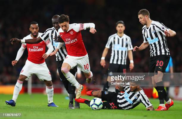 Mesut Ozil of Arsenal evades Mohamed Diame, Deandre Yedlin and Florian Lejeune of Newcastle United during the Premier League match between Arsenal FC...