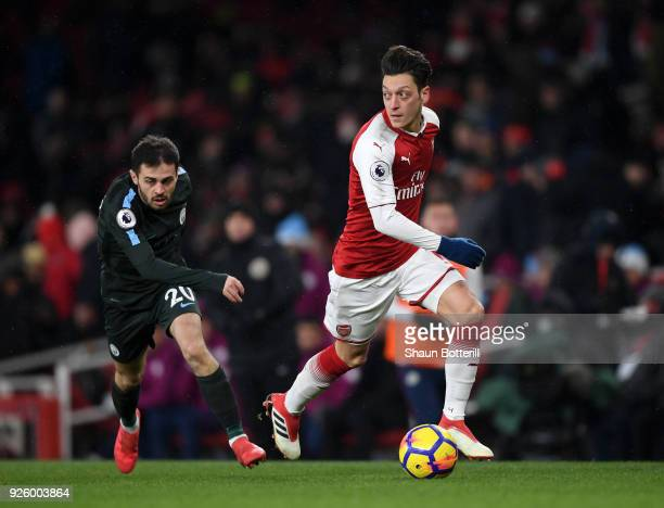 Mesut Ozil of Arsenal gets to the ball ahead of Bernardo Silva of Manchester City during the Premier League match between Arsenal and Manchester City...