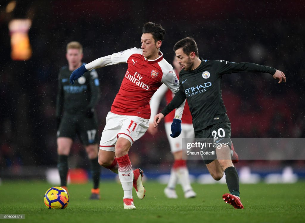 Mesut Ozil of Arsenal gets to the ball ahead of Bernardo Silva of Manchester City during the Premier League match between Arsenal and Manchester City at Emirates Stadium on March 1, 2018 in London, England.