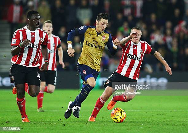 Mesut Ozil of Arsenal goes between Victor Wanyama and Jordy Clasie of Southampton during the Barclays Premier League match between Southampton and...