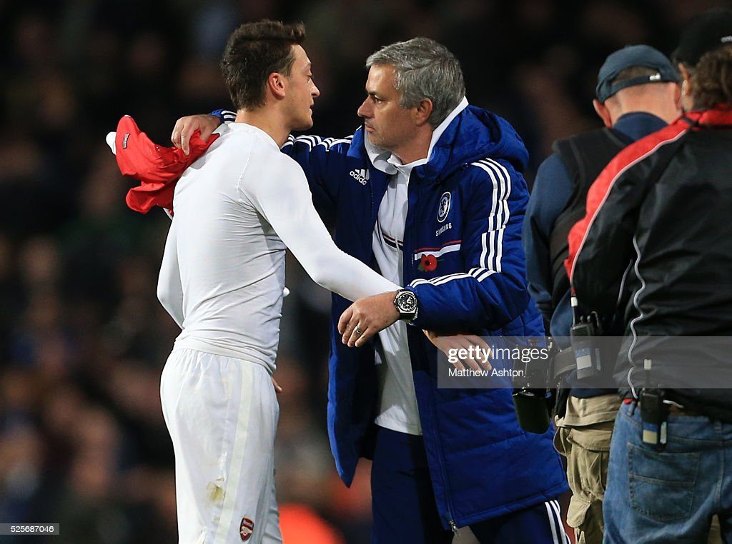 Mesut Ozil of Arsenal hands his shirt to Jose Mourinho the head coach / manager of Chelsea at the end of the match who then gives him a hug