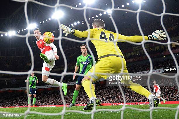 Mesut Ozil of Arsenal has his shot saved Fraser Forster of Southampton during the Barclays Premier League match between Arsenal and Southampton at...