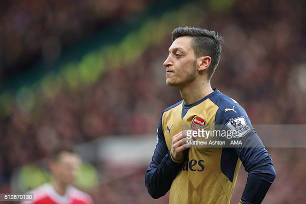 Mesut Ozil of Arsenal holds his Arsenal badge on his shirt during the Barclays Premier League match between Manchester United and Arsenal at Old...