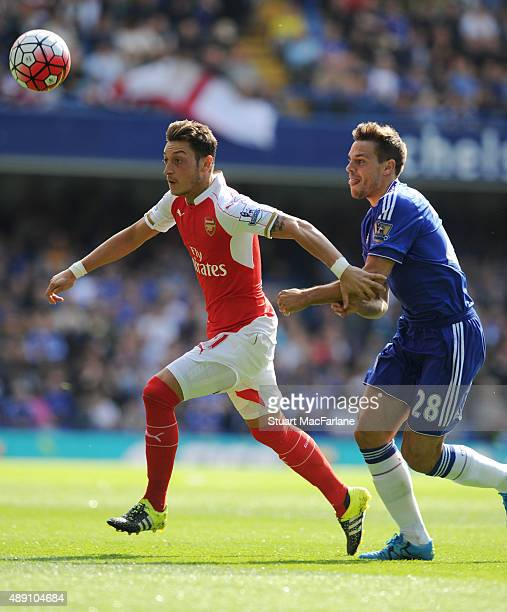 Mesut Ozil of Arsenal holds off Cesar Azpilicueta of Chelsea during the Barclays Premier League match between Chelsea and Arsenal on September 19...