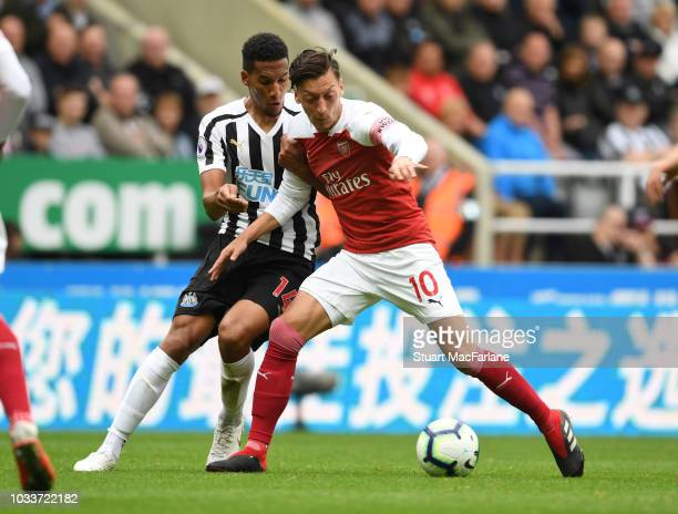 Mesut Ozil of Arsenal holds off Issac Hayden of Newcastle during the Premier League match between Newcastle United and Arsenal FC at St James Park on...