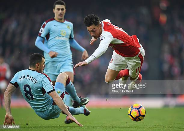Mesut Ozil of Arsenal is challenged by Dean Marney of Burnley during the Premier League match between Arsenal and Burnley at the Emirates Stadium on...