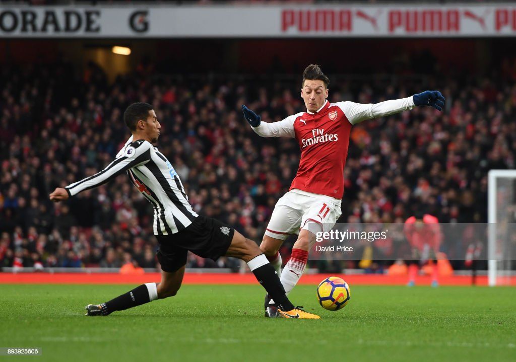 Mesut Ozil of Arsenal is challenged by Isaac Hayden of Newcastle during the Premier League match between Arsenal and Newcastle United at Emirates Stadium on December 16, 2017 in London, England.